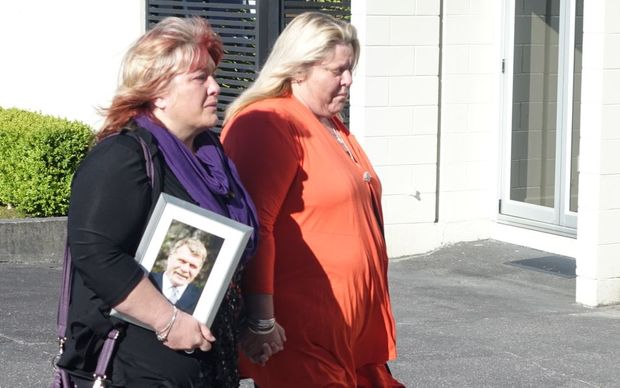 Anna Osborne (left), arrives for the meeting carrying a picture of her husband Milton who died in the mine.