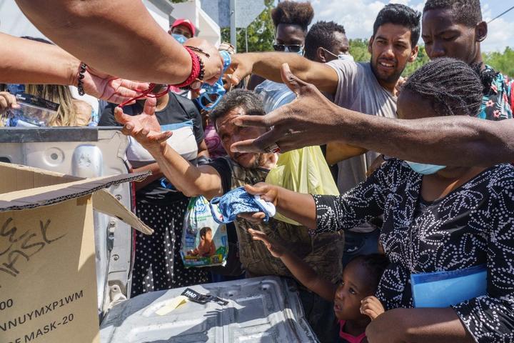 Los migrantes reciben máscaras faciales cerca del puerto de entrada del Río Acuña.