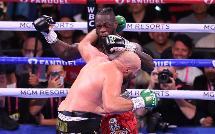 WBC heavyweight champion Tyson Fury of Great Britain (L) and US challenger Deontay Wilder (R) exchange punches during a fight for the WBC/Lineal Heavyweight title at the T-Mobile Arena in Las Vegas, Nevada, October 9, 2021. (Photo by Robyn Beck / AFP)