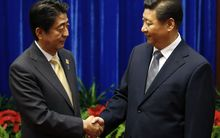 China's President, Xi Jinping, right, shakes hands with Japan's Prime Minister, Shinzo Abe.