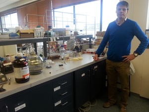 A photo of Shane Telfer at his work bench in the lab