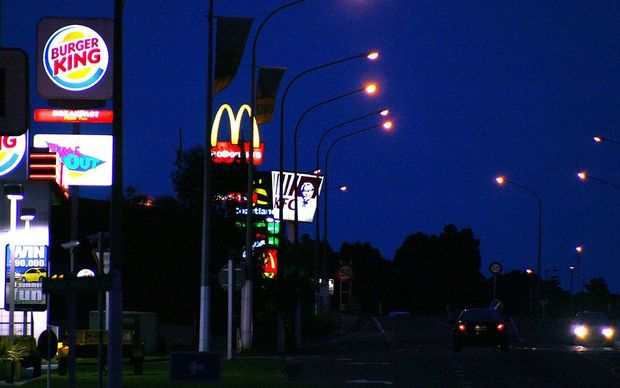 Fast food outlet illuminated signs beside State Highway 1 at night, Paraparaumu