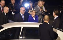 Germany's Chancellor Angela Merkel (C) is welcomed upon her arrival at the airport in Brisbane to take part in the G20 summit on 14 November 2014.