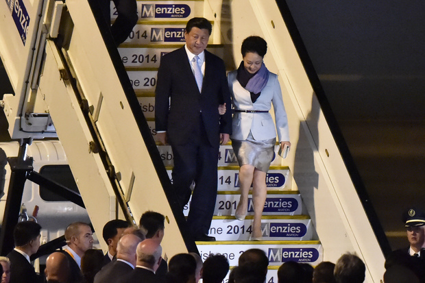 China's President Xi Jinping and his wife Peng Liyuan walk down from their plane upon their arrival in Brisbane.