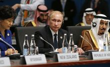 Vladimir Putin (C) looks up as South Korean President Park Geun-hye (L) and Saudi Arabia Crown Prince Salman bin Abdulaziz (R) listen at the start of the plenary session at the G20 Summit.