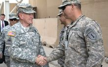 Martin Dempsey shakes hands with US service members in Baghdad, Iraq.