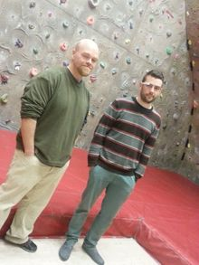 A photo of Deak Helton standing in front of the climbing wall, with Alex Woodham wearing Google Glass
