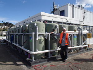 Stan Abbott stands next to the Roof Water Research Centre on the roof of Massey University in Wellington, which comprises 16 large water tanks and a sophisticated weather monitoring system.
