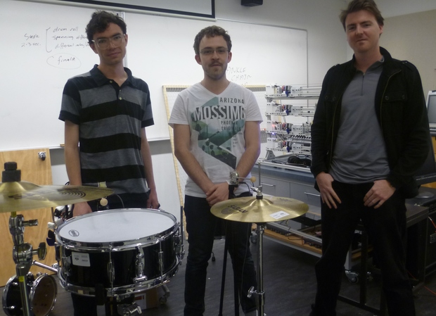 Jim Murphy (left), James McVay (centre) and Jason Long (right) standing behind the robotic drum kit. The MechBass robotic bass guitar is at the back, between James and Jason.