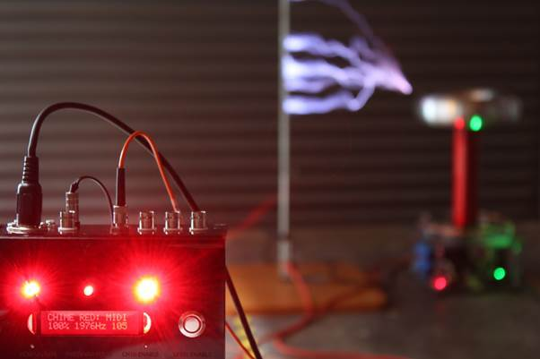 The lightning arcs produced by the Tesla coils are controlled by the Chime Red box pictured in front. The faster the coil is fired, the higher the pitch of the resulting sound.