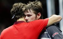 Roger Federer (L) and Stan Wawrinka embrace after their match.