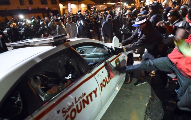 Protesters attack a police car during clashes following the grand jury decision in the death of 18-year-old Michael Brown in Ferguson, Missouri.