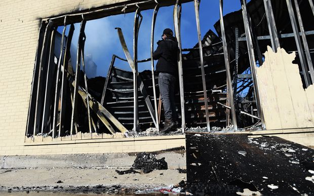 A journalist photographs a burnt-out store in Ferguson, Missouri, which was set ablaze following the grand jury decision.