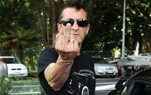 Phil Rudd gestures to media as he leaves court.