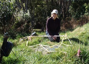 Alison Cree behind a tuatara nest, which is marked with tape to prevent people walking on it (it's on a gravel track) and watched over by a remote camera.