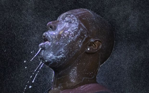 A man is doused with milk and sprayed with mist after being hit with tear gas during demonstrations on the grand jury's decision not to charge officer who shot Michael Brown.