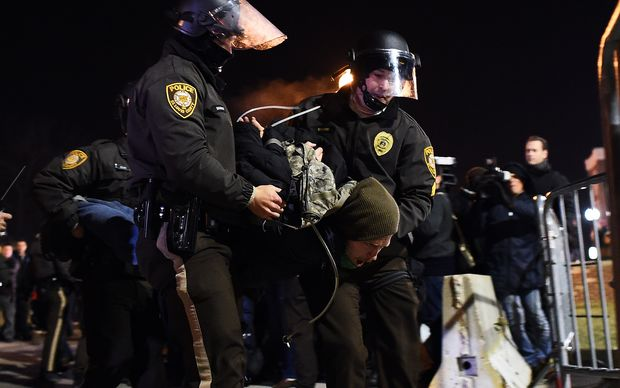 Police arrest a protester in Ferguson, Missouri, during demonstrations a day after violent protests and looting following the grand jury decision.