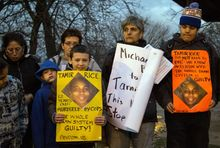 People display sigs at Cudell Commons Park in Cleveland, Ohio, during a rally for Tamir Rice.