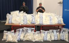 Officers stand near packages containing illicit drugs during a press conference in Sydney on 29 November 2014.