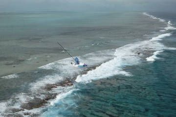 Team Vestas Wind a competitor in the Volvo Ocean race lies on a reef in the India Ocean.