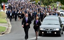 A large procession of mourners follows the hearse carrying Phillip Hughes.