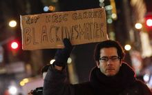 "A protester in New York City holds a banner reading ""Black Lives Matter"" as he takes part in a rally over the death of Eric Garner."