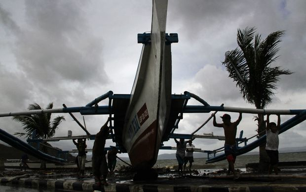 Fishermen carry an outrigger to higher ground in Legazpi City, south of Manila, on 5 December 2014, ahead of the landfall of Typhoon Hagupit.