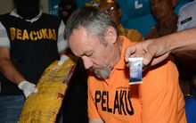 Antony de Malmanche of New Zealand sits as evidence is placed next to him during a press conference in Denpasar, Bali.