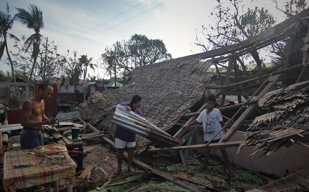 A family salvages roof materials from their destroyed house in Dolores town, Eastern samar.