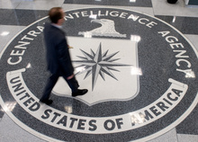 A man walking across the Central Intelligence Agency (CIA) logo in the lobby of CIA Headquarters in Langley, Virginia.