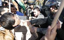 An Israeli border guard grabs Palestinian official Ziad Abu Ein (L) during a demonstration in the village of Turmus Aya near Ramallah, on 10 December 2014.