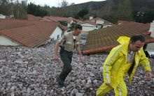 Houses are damaged after heavy rain triggered a mudslide in Ventura County, California on 12 December 2014 (local time).