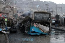 Afghan security personnel inspect a damaged bus at the site of a suicide attack by the Taliban in Kabul, Afghanistan.