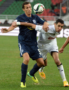 Auckland City FC's Angel Berlanga (L) fights for the ball with ES Setif's Ahmed Gasmi (R).