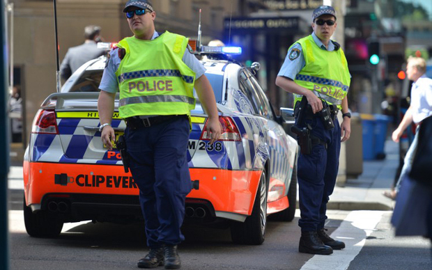Police close a street where a cafe is being used to hold hostages in the central business district of Sydney