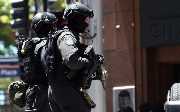 Armed police run toward a cafe in the central business district of Sydney