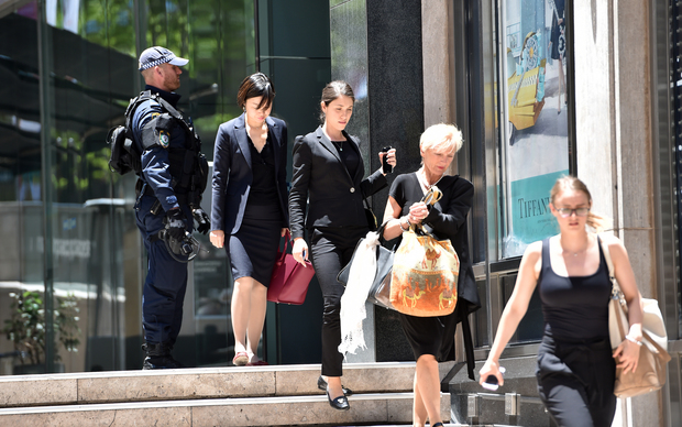 Armed police evacuate employees from the offices next to a cafe in the central business district of Sydney
