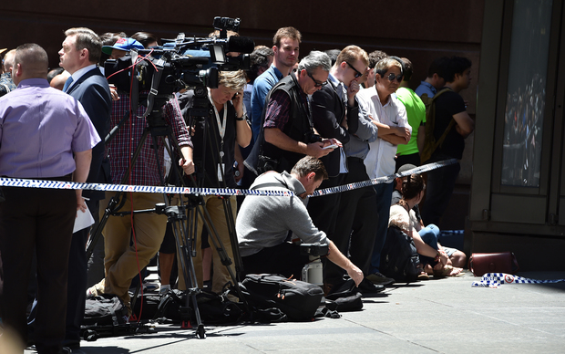 Members of the media monitor the situation near a cafe in the central business district of Sydney