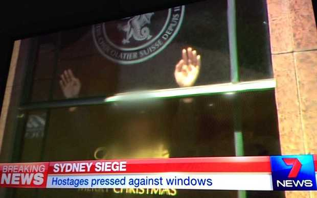 A hostage in the Sydney cafe with their hands on the window.