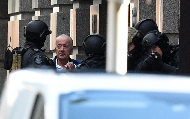 A released hostage (second from left), speaks with NSW Public Order and Riot Squad Police.