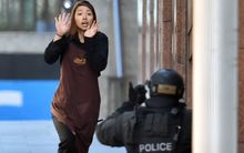 A young woman flees after being held hostage in a central Sydney cafe.