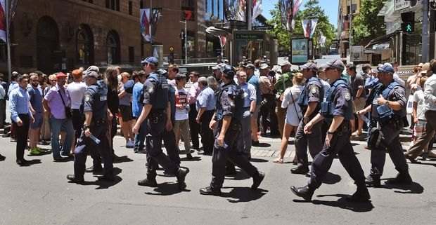 Police walk through Martin Place as spectators look on during a hostage siege.