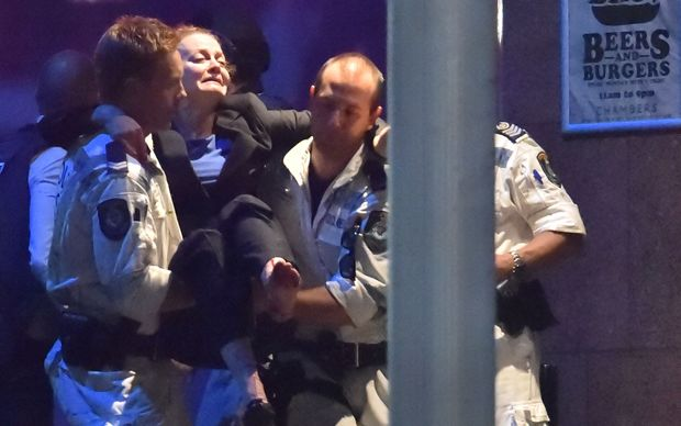 An injured hostage is carried out of the Lindt Chocolate Cafe in Sydney's Martin Place
