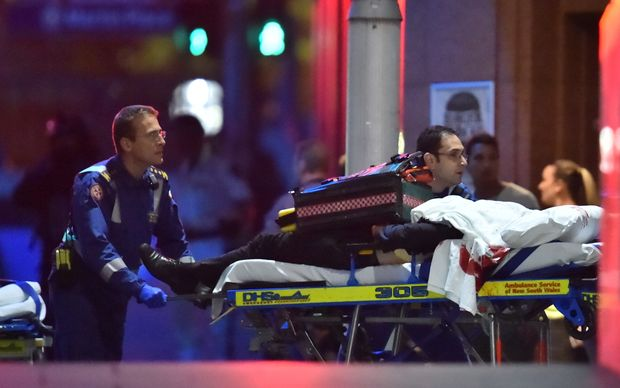Paramedics take a person on a stretcher out of the Lindt cafe in Sydney's Martin Place.