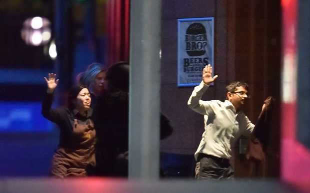 Hostages run out of the a cafe in the central business district of Sydney.