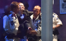 An injured hostage is carried out of a Sydney cafe at the centre of the hostage crisis.