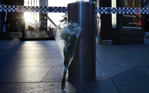 A bunch of flowers rests beside a bollard near the Lindt chocolate cafe in Martin Place following the siege.