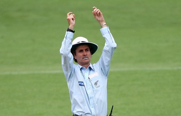 New Zealand cricket umpire Billy Bowden signals a six.