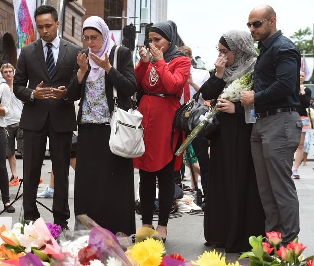 Representatives of the Muslim community pray after laying flowers at a floral memorial at the scene of the Sydney siege.