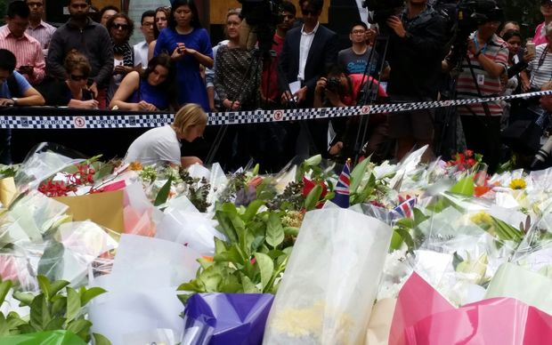 A woman adds her tribute to a sea of flowers in Sydney Martin Place.